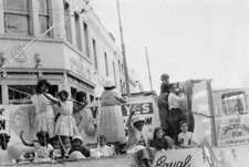 Aboriginal rights activist and community worker Aunty Celia Smith (in hat with back to camera) with Granny Monsell (waving) on May Day float campaigning for a 'YES' vote in the 1967 Referendum, Brisbane, 1967.